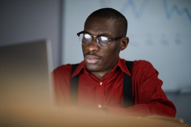 Empresario africano usando laptop en la oscura oficina