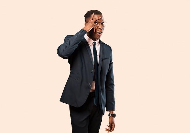 Empresario afroamericano conmocionado, asustado o aterrorizado, cubriéndose la cara con la mano y mirando entre los dedos contra la pared beige