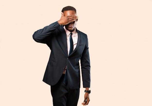 Empresario afroamericano cubriendo los ojos con una mano sintiéndose asustado o ansioso, preguntándose o esperando ciegamente una sorpresa contra la pared beige