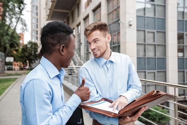 Empresario afroamericano y empresario caucásico sonriendo y hablando