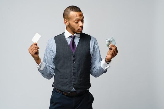 Empresario afroamericano haciendo elección entre tarjeta de crédito y dinero
