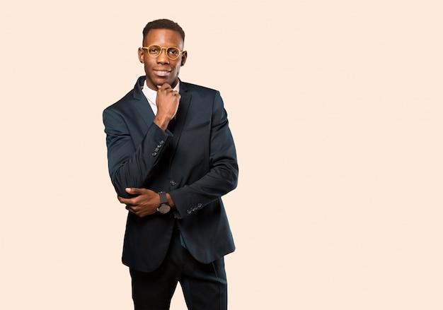 Empresario afroamericano que parece feliz y sonriente con la mano en la barbilla, preguntándose o haciendo una pregunta, comparando opciones contra la pared beige