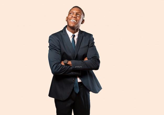 Empresario afroamericano se siente feliz, orgulloso y esperanzado, preguntándose o pensando, mirando hacia arriba para copiar el espacio con los brazos cruzados contra la pared de color beige