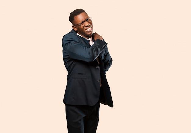 Empresario afroamericano sintiéndose cansado, estresado, ansioso, frustrado y deprimido, sufriendo dolor de espalda o cuello contra la pared beige