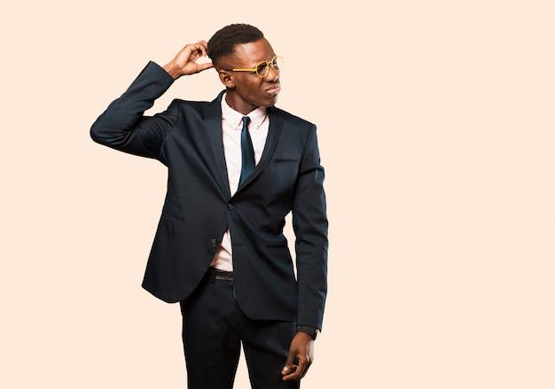 Empresario afroamericano sintiéndose perplejo y confundido, rascándose la cabeza y mirando hacia un lado contra la pared beige