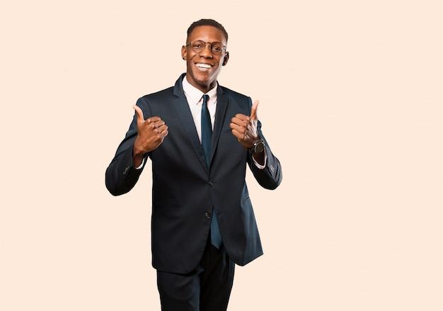 Empresario afroamericano sonriendo alegremente y luciendo feliz, sintiéndose despreocupado y positivo con ambos pulgares contra la pared beige