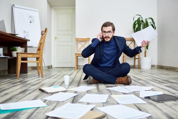 Empresario agitado trabajando en el piso en la oficina