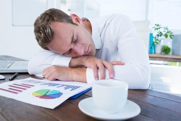 Empresario agotado durmiendo en el escritorio