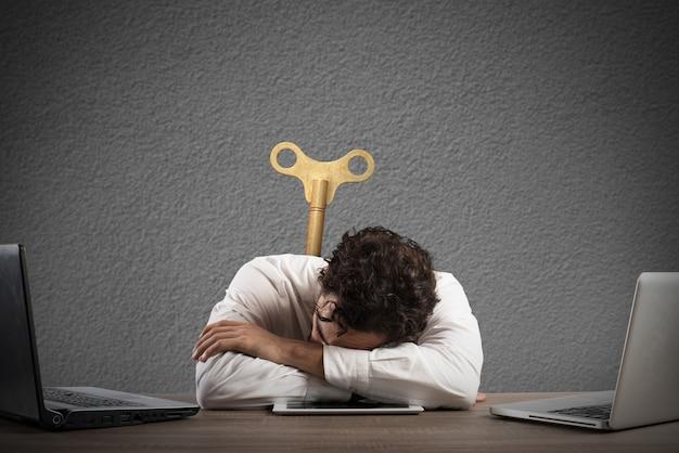 Empresario agotado por exceso de trabajo durmiendo sobre una tableta