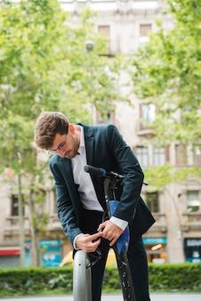 Empresario ajustando la correa de scooter eléctrico