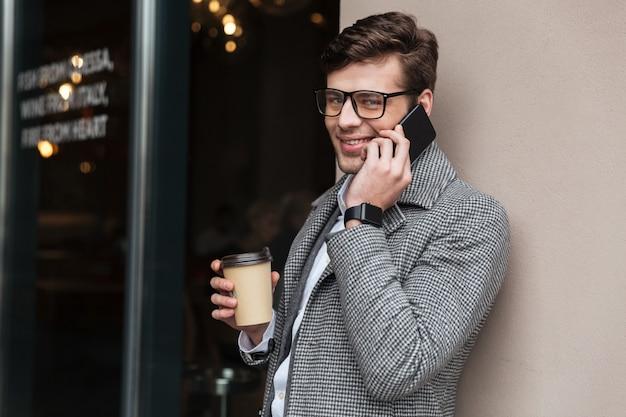 Empresario alegre en anteojos y abrigo hablando por teléfono inteligente