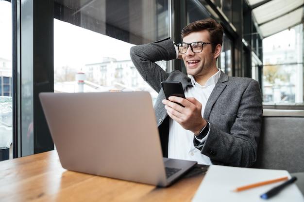 Empresario alegre en anteojos sentado junto a la mesa en la cafetería con computadora portátil y teléfono inteligente mientras sostiene la cabeza y mira a otro lado