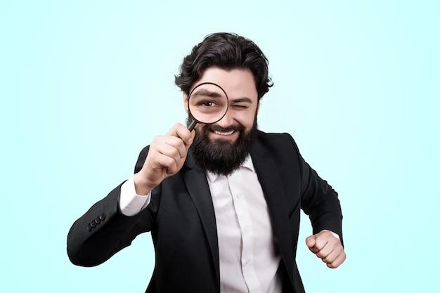 Empresario alegre barbudo con lupa sobre pared azul, concepto de búsqueda