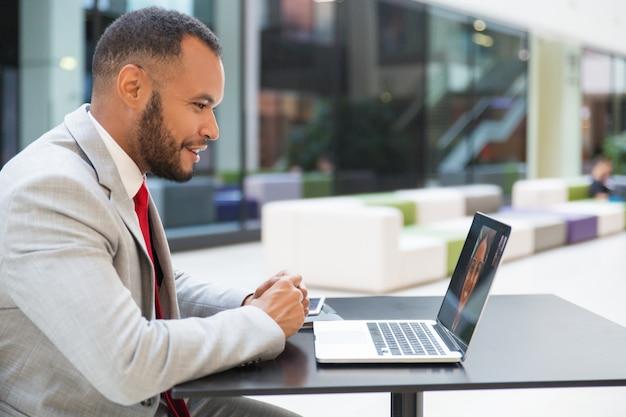 Empresario alegre chateando vía laptop