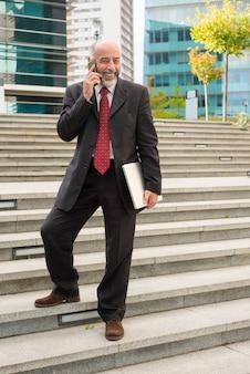 Empresario alegre con smartphone y laptop
