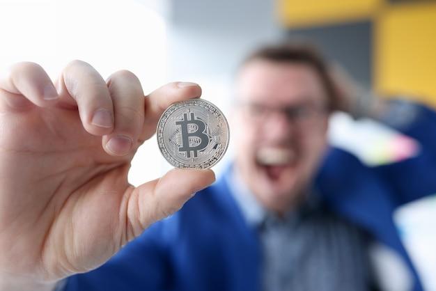 Empresario alegre sosteniendo una moneda con bitcoin