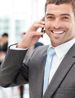 Empresario alegre en el teléfono durante una reunión con su equipo