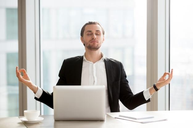 Empresario alivia el estrés laboral con la meditación.