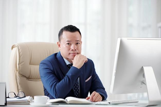 Empresario ambicioso planeando su futura carrera sentado en la mesa de la oficina