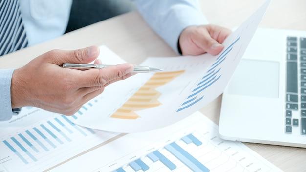 El empresario analiza el gráfico con el portátil en la oficina para establecer objetivos comerciales desafiantes
