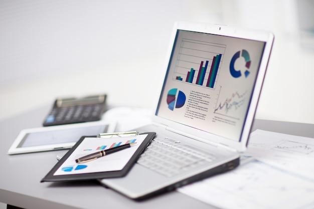 Empresario analizando gráficos de inversión con ordenador portátil. contabilidad