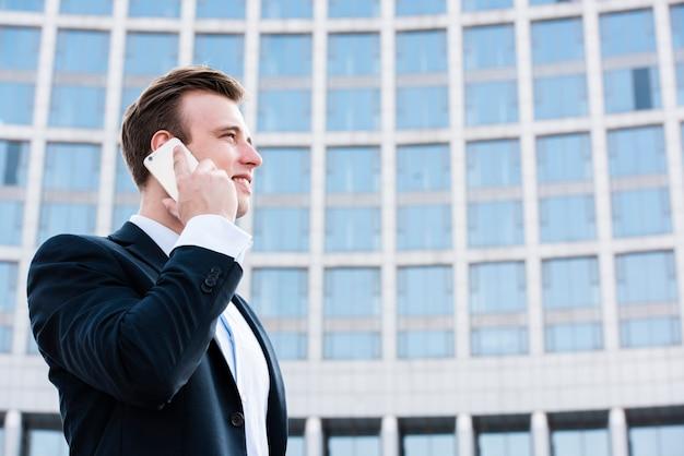 Empresario de bajo ángulo hablando por teléfono