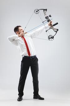 Empresario apuntando al blanco con arco y flecha, aislado sobre fondo blanco.