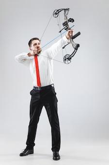 Empresario apuntando al objetivo con arco y flecha, aislado en la pared gris del estudio