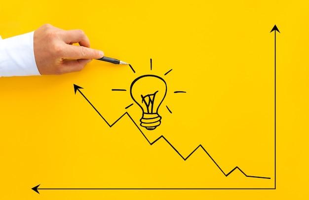 Empresario apuntando crecimiento de bombilla y flecha con lápiz. objetivos de puesta en marcha de empresas para el éxito