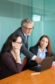 Empresario apuntando a la pantalla y mostrando los detalles del proyecto a un colega.