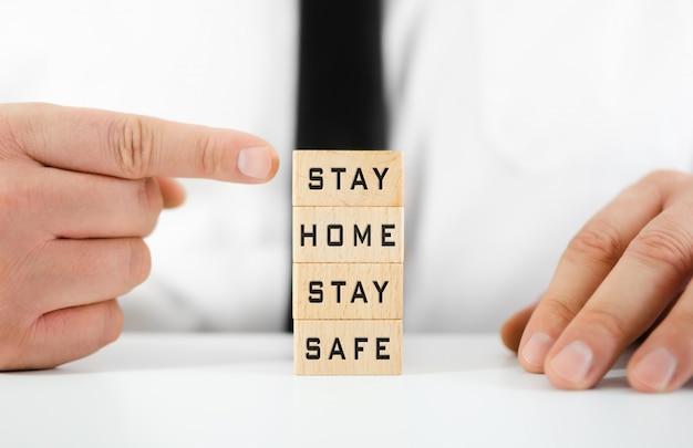 Empresario apuntando a stay home, stay safe escrito en bloques de madera en una imagen conceptual para tiempos de cuarentena durante el brote de virus.