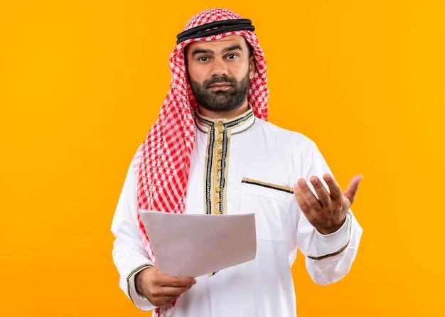Empresario árabe en documentos tradicionales wearholding con el brazo hacia fuera haciendo una pregunta de pie sobre la pared naranja