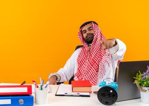 Empresario árabe en ropa tradicional sentado en la mesa apuntando con el dedo trabajando en la oficina