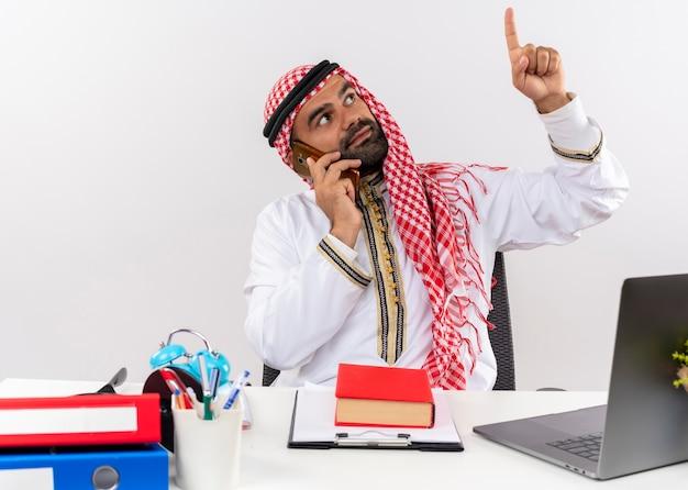 Empresario árabe en ropa tradicional sentado en la mesa hablando por teléfono móvil apuntando hacia arriba con el dedo trabajando en la oficina