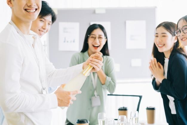 El empresario asiático abre champagne para celebrar el año nuevo con los miembros del grupo empresarial