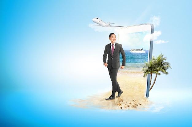Empresario asiático caminando por la playa