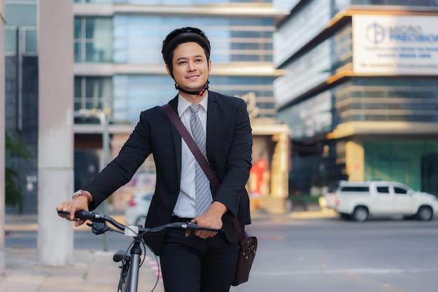 Empresario asiático empujando su bicicleta desde casa