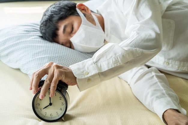 Empresario asiático con máscara quirúrgica durmiendo en la cama con reloj despertador