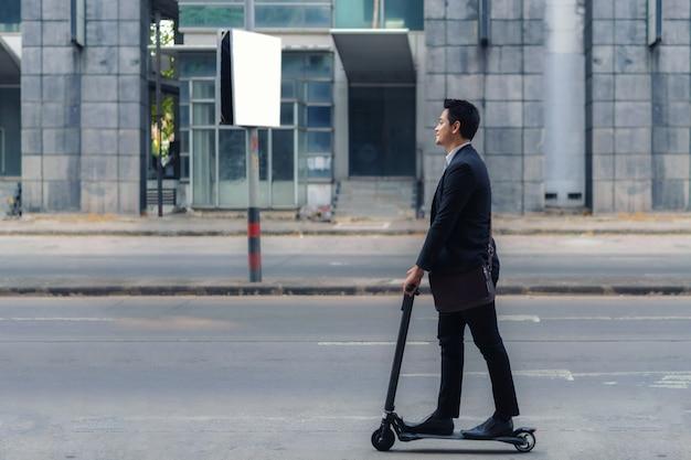 Empresario asiático montando un scooter eléctrico en las calles de la ciudad para ir a trabajar por la mañana