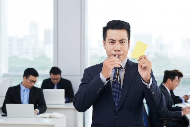Empresario asiático mostrando tarjeta amarilla