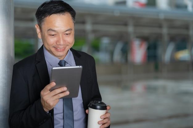 Empresario asiático de pie y sosteniendo una tableta digital con edificios de oficinas comerciales en la ciudad