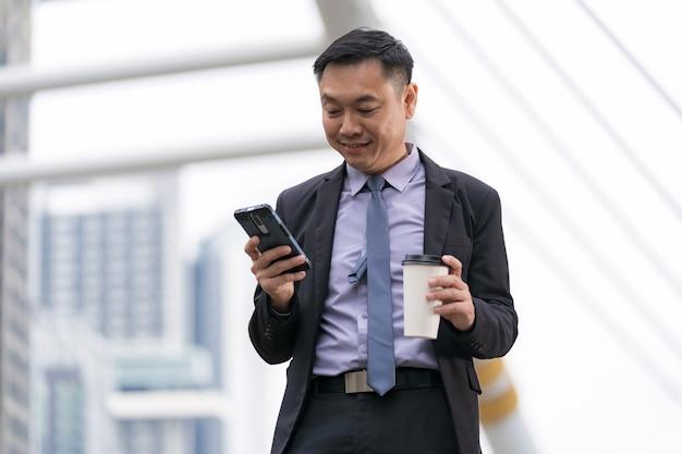 Empresario asiático de pie y sosteniendo teléfono móvil