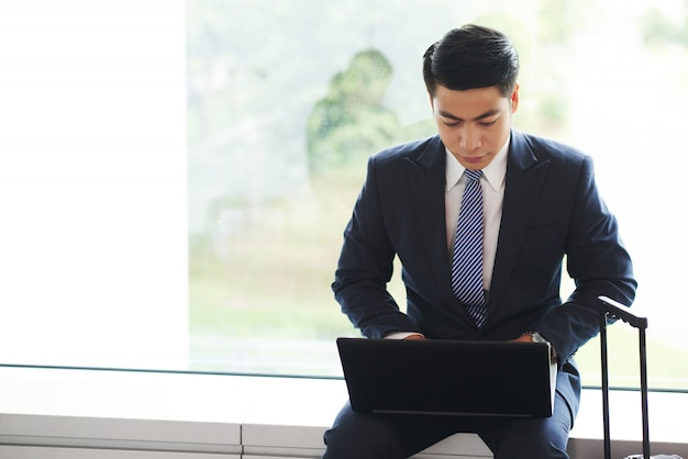 Empresario asiático sentado en el alféizar de la ventana, con el asa de la maleta mostrando y trabajando en la computadora portátil