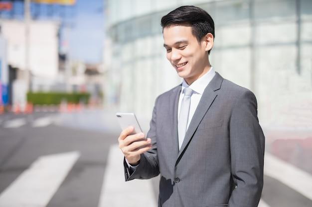 Empresario asiático sonríe y usa un teléfono inteligente