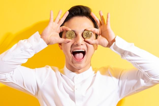 Empresario asiático sosteniendo bitcoin en su mano con cara feliz