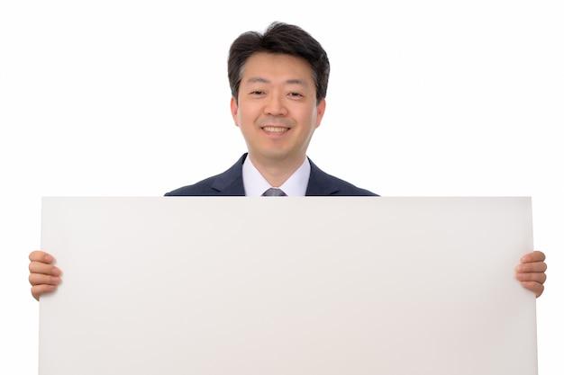 Un empresario asiático con un tablero de mensajes en blanco.
