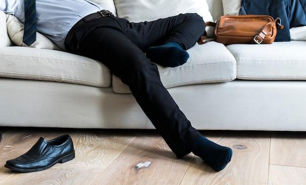 Empresario asiático tomando descanso tendido en el sofá