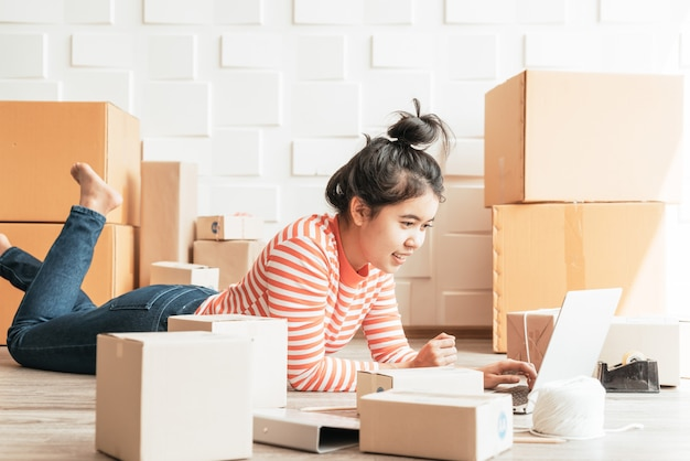Empresario asiático trabajando en casa con caja de embalaje en el lugar de trabajo