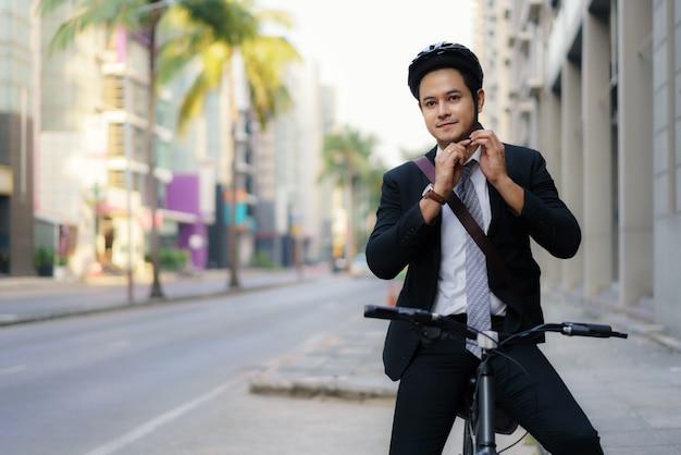 El empresario asiático en trajes lleva cascos de seguridad para andar en bicicleta por las calles de la ciudad