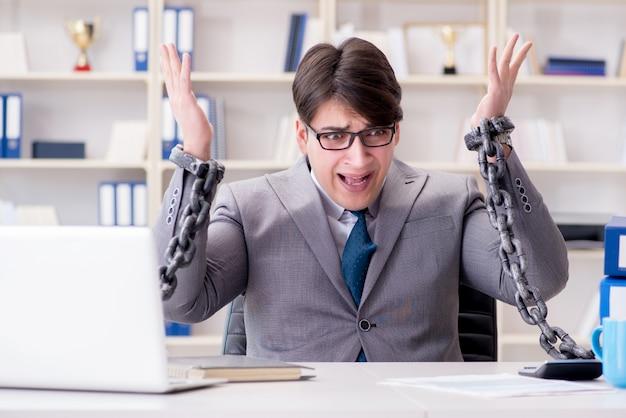 Empresario atado con cadenas a su trabajo